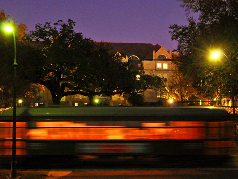 A blurred St. Charles streetcar going past Gibson Hall after twilight.
